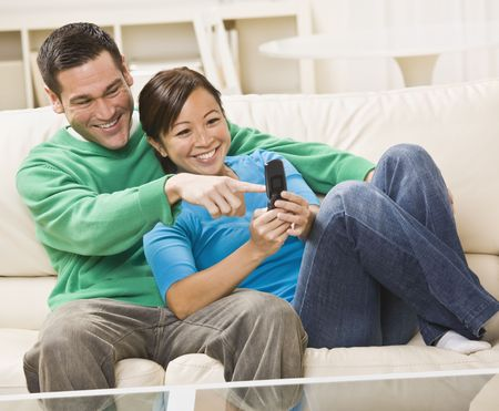 couple on couch: Mixed race couple watching TV on couch with remote control. horizontal