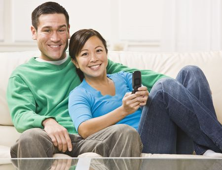 and the horizontal man: An attractive young couple sitting on a couch and watching television.  They are smiling directly at the camera.  The female is holding a remote.  Horizontally framed photo.