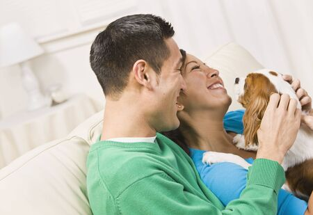An attractive young couple sitting on a couch together and holding a dog.  They are laughing.  Horizontally framed shot. photo