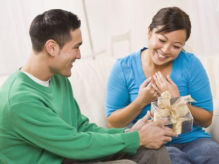 ソファに座っている魅力的な若いカップル。男性は、女性に贈り物を提示されています。両方は、彼らが笑っています。水平方向にフレーム ショット。
