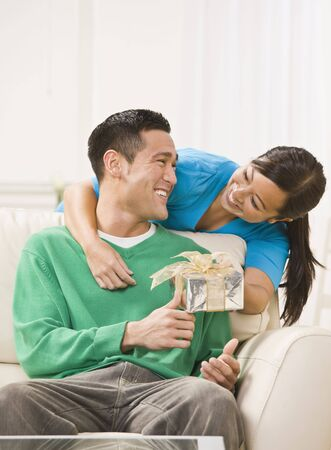 An attractive young exchanging a gift.  They are smiling directly at one another. Vertically framed photo.