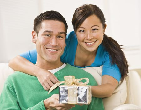 A young couple is seated together on their couch.  They are holding a present and are smiling at the camera.  Horizontally framed shot.