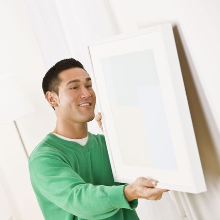 Asian male wearing a green sweater hanging art on wall. Square composition Stock Photo - 5119633