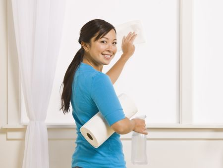 sufficient: An attractive asian young female washing a window. She is holding a roll of paper towels and has her head turned to smile toward the camera. Horizontally framed photo.