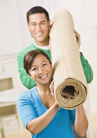 sufficient: A happy and attractive young couple carrying a roll of carpet together.  They are smiling at the camera.  Vertically framed shot.