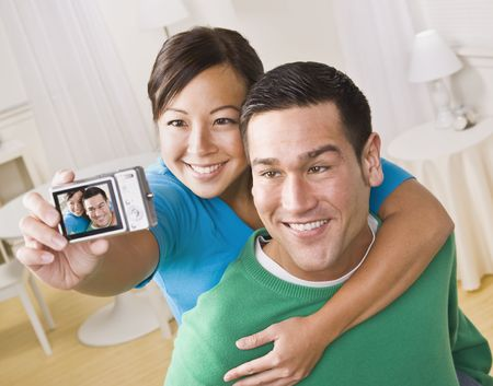 digital eye: An attractive young couple taking their own picture with a digital camera. They are smiling.  The female is holding the camera. Horizontally framed shot.