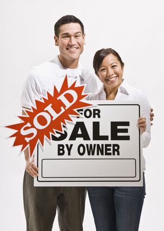 Attractive couple holding sold sign for home. Vertically framed Stock Photo - 5120856