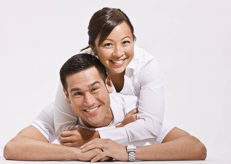 An attractive young couple posing together on the floor.  They are smiling directly at the camera.  Horizontally framed shot.