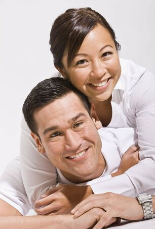 Attractive asian couple hugging with woman on top.vertical photo