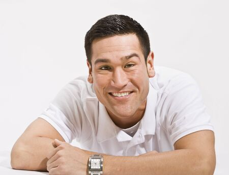 A young man is isolated in a white room.  He is wearing a white T-shirt and is smiling at the camera.  Horizontally framed shot. photo