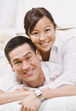 An attractive young couple posing.  They are wearing white and are looking directly at the camera. Vertically framed photo. Stock Photo