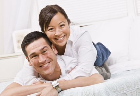 A happy and attractive young couple posing together.  They are lying down and are smiling at the camera. Horizontally framed shot.