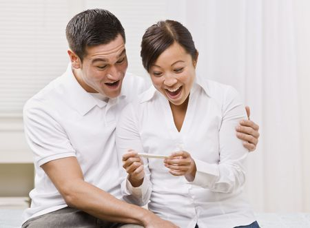 procreation: Attractive couple surprised and overjoyed reading pregnancy test. Square composition Stock Photo