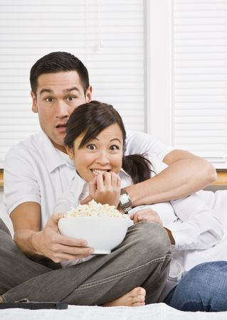 they are watching: A young, attractive couple is sitting together in bed and watching TV.  They look shocked or scared, and are looking at the camera. Horizontally framed shot.