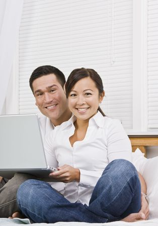 Attractive Asian couple sitting together with laptop. Vertically framed shot.