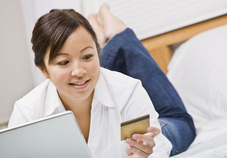 An attractive young woman lying on a bed and gazing at a credit card.  She is holding a laptop and is smiling. Horizontally framed photo. Stock Photo