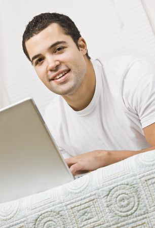 A young man lying on a bed and using a laptop computer.  He is smiling and is facing the camera. Vertically framed shot. photo