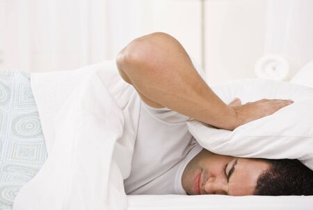 pained: A tired looking man holding a pillow over his head and lying in bed.  Horizontally framed shot.