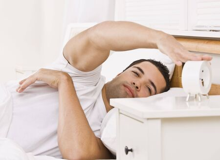 A man lying in bed.  He is reaching his arm to touch an alarm clock.  He looks tired. Horizontally framed shot. photo