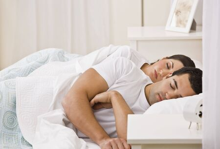 An attractive young couple sleeping. They have their eyes closed. Horizontally framed shot.