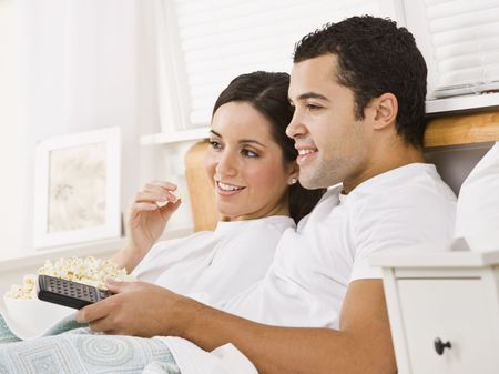 they are watching: An attractive young couple lying in bed and watching television.  They have a bowl of popcorn and a remote. They are smiling. Horizontally framed photo.