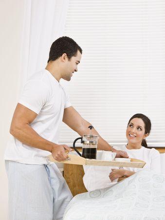 朝食をトレイの上、ベッドの中で美しい女性魅力的な男。彼らはお互いの愛情を込めて見つめています。垂直方向にフレームのショット。