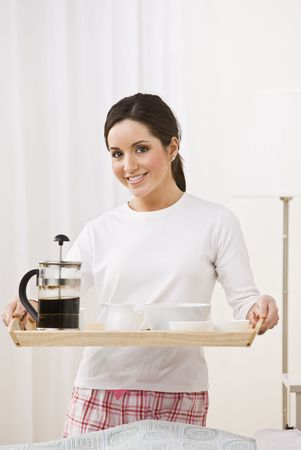 A young, attractive woman is standing in her pajamas and is holding a breakfast tray.  She is smiling at the camera.  Vertically framed shot. photo