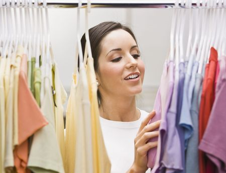 An attractive young female looking through a clothing closet.  She is smiling.  Horizontally framed photo. Stock Photo