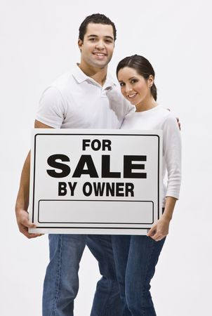 An attractive, young couple holding a For Sale By Owner sign.  They are smiling and are looking directly at the camera. Vertically framed shot. Stock Photo