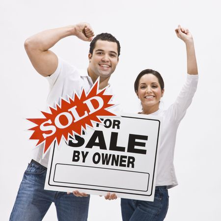 Happy Couple with sold sign for home pumping their fists in the air in celebration. Square composition.