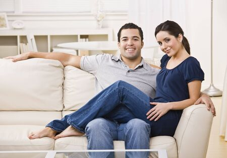 An attractive young couple lounging on a couch together.  The female is sitting on the male's lap.  They are facing the camera and are smiling. Horizontally framed photo. Stock Photo - 5120735