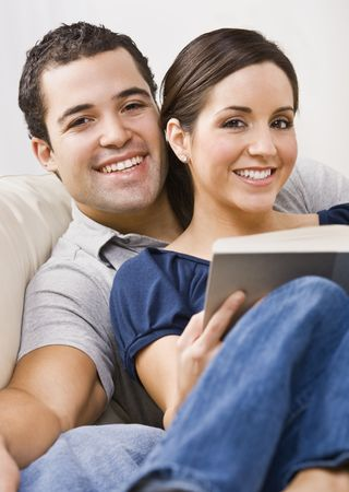 An attractive young couple relaxing together.  The female is holding a book and they are smiling directly at the camera. Vertically framed photo. photo