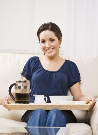 A beautiful young woman sitting on a couch and holding a breakfast tray.  She is smiling at the camera.  Vertically framed shot. photo