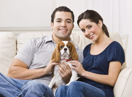 serene people: Attractive couple with their dog on their living room couch. horizontal