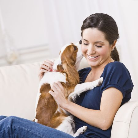 An attractive young woman sitting on a couch and being kissed by a dog that she is holding.  She is smiling and her eyes are closed. Square framed photo. photo