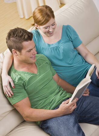 一緒と本から読書ソファに座って魅力的な若いカップル。彼らが笑っています。垂直方向にフレームのショット。
