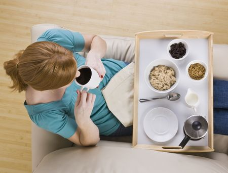 1 person: A woman sitting with a breakfast tray on her lap.  She is drinking coffee. Horizontally framed shot. Stock Photo