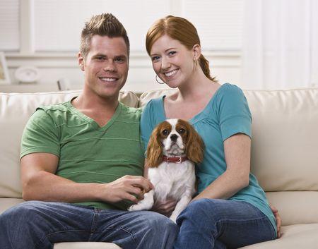 若くて魅力的なカップルは一緒に座っていると、犬を保持しています。 彼らはカメラに直面しているし、笑っています。水平方向に組み立てられた写真。