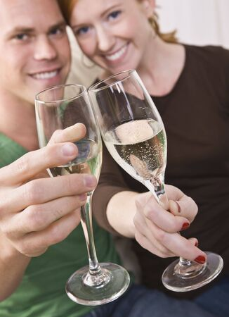 An attractive young couple toasting champagne flutes happily. They are smiling at the camera. Vertically framed shot. photo