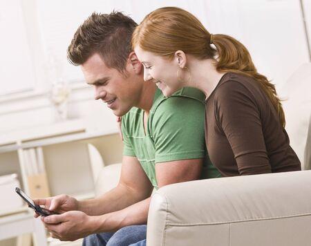 携帯電話を表示する魅力的な若いカップル。彼らは笑っているし、ソファの上が装着されています。水平方向に組み立てられた写真。