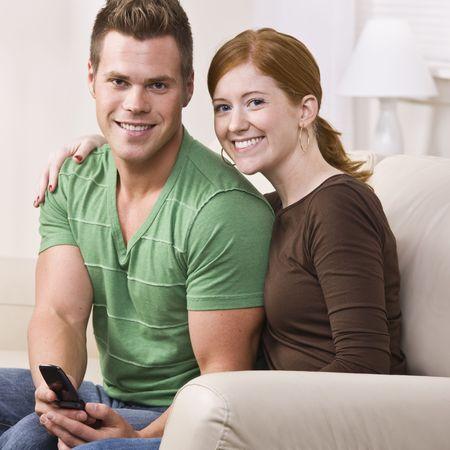 魅力的な若いカップル、ソファに座っていると笑みを浮かべてします。彼らはカメラを見て直接。男性は、携帯電話を保持しています。正方形の組成物。
