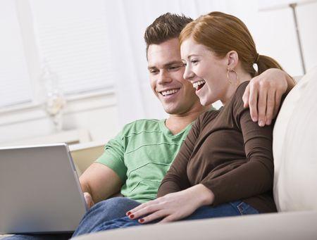 若くて魅力的なカップルは一緒に座って、ノート パソコンの画面を表示します。笑って、笑っています。水平方向に組み立てられた写真。