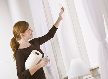 Attractive woman cleaning window holding paper towel. horizontal Stock Photo