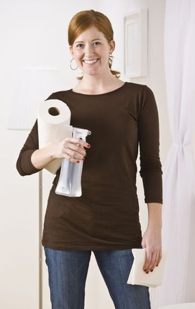 An attractive young woman holding cleaning supplies.  She is smiling directly at the camera. Vertically framed photo. photo