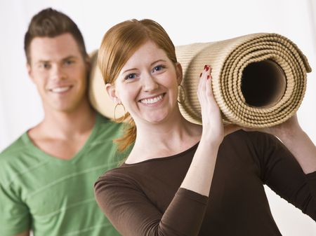 sufficient: A young, attractive couple is carrying a roll of carpet.  They are smiling at the camera.  Horizontally framed shot.