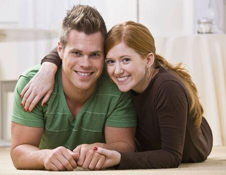 一緒に彼らのアパートの床に横たわって若い、魅力的なカップル。彼らは彼らの胃にリラックスしているし、カメラを見て笑っています。水平方向にフレームの写真。