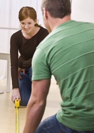 Attractive couple measuring floor with tape measure. vertical photo
