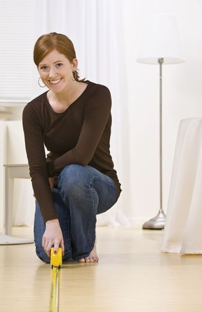 sufficient: Smiling woman kneeling while measuring the floor, vertically framed