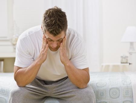 sick: Un hombre est� sentado en la cama en un dormitorio. �l tiene su cabeza en sus manos y est� buscando fuera de la c�mara. Horizontalmente enmarcada disparo. Foto de archivo
