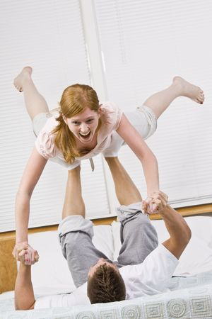 A couple playing on a bed.  The male is balancing the female in the air with his feet. She is laughing.  Vertically framed photo. photo